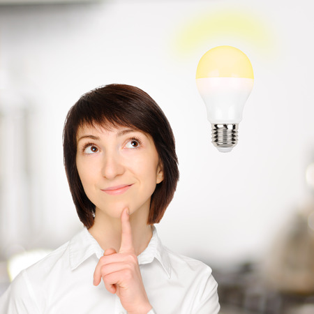 Beautiful business woman with idea light bulb above.