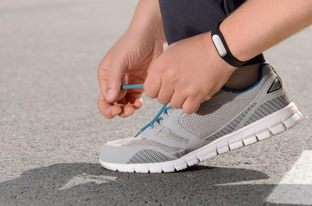 sport equipment: Hand wearing fitness tracker tying shoelaces on asphalt road