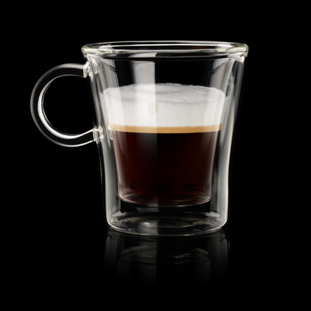 Coffee espresso macchiato in transparent cup on black background Фото со стока
