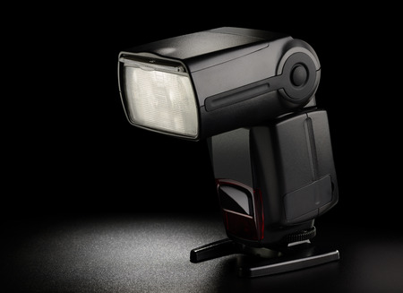 Photo camera flash on black background. Low key technique Reklamní fotografie