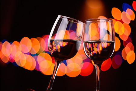 clink: Two wine glasses clink at the party, background with blurred lights