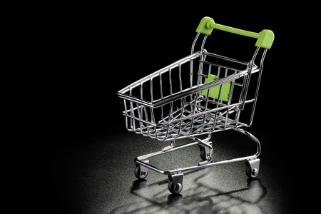 shopping buggy: Shopping cart with green handle on a black textured background with copy-space