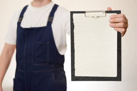overall: Courier in overall holding empty clipboard in his hand over white background