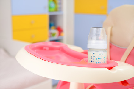 baby girl pink: Baby pink high chair and bottle with milk in baby room