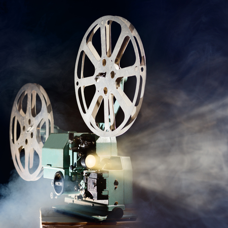 movie reel: Old retro movie projector with smoke and light beam