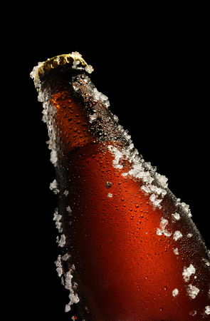 dew cap: Cold brown bottle of beer with water droplets and ice over black background Stock Photo