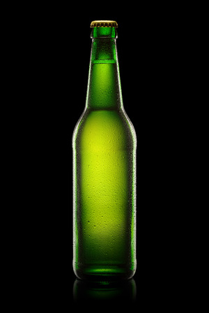 dew cap: Green wet Bottle of beer isolated on black background. With clipping path. Stock Photo