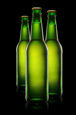 dewed: Three green wet bottles of beer on black background.