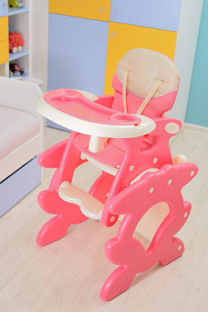 high chair: Baby pink high chair on the floor of babys room