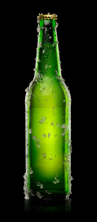 dewed: Green Bottle of beer with ice crystals isolated on black background. With clipping path. Stock Photo