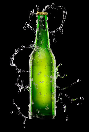 dew cap: Green Bottle of beer with ice crystals on black background with water splash Stock Photo