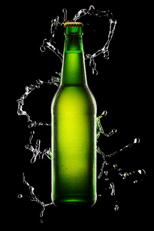 dewed: Green wet Bottle of beer on black background with water splash