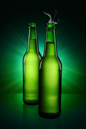 dewed: Two opened green wet bottles of beer with steam on neck over green background. Stock Photo