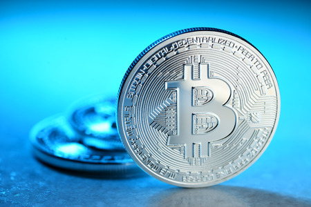 decentralized: Silver Bitcoin coin on blue background. Electronic money, cryptocurrency Stock Photo
