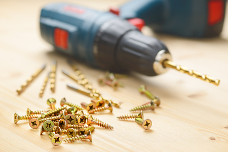 Heap of metal screws and electric drill in wooden board Stock Photo