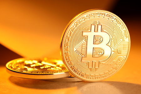 decentralized: Golden Bitcoin coin on yellow background. Electronic money, cryptocurrency