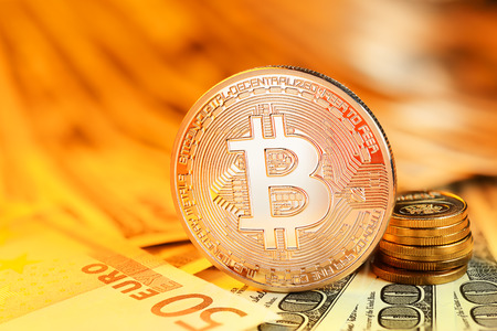 decentralized: Golden Bitcoin coin on different currency bills. Electronic money exchange concept Stock Photo