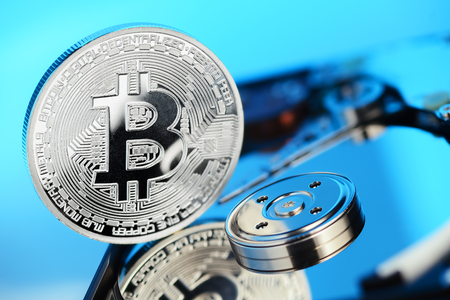 decentralized: Silver Bitcoin coin on the opened HDD disk. Electronic money, cryptocurrency Stock Photo