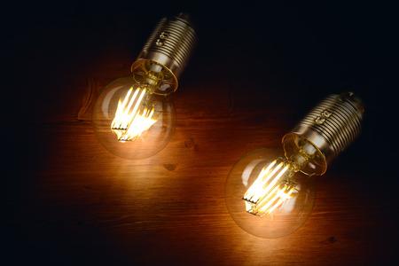 Dwie diody klasyczne żarówki żarnika stylizowany na desce tle.