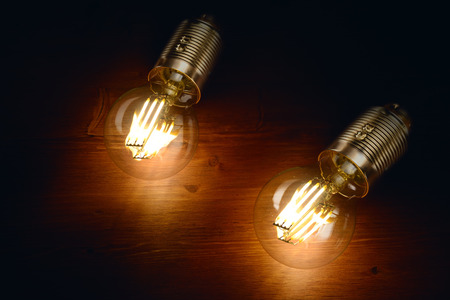 Two LED filament classic styled bulbs on wooden board background. Stock Photo
