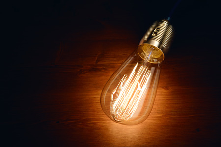 incandescence: Edison incandescence classic styled bulb on wooden board background. Stock Photo
