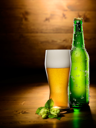 fizz: Glass and bottle of beer with hop on wood background. Empty space for text