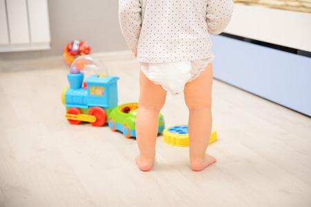 Baby walking on wooden floor in diaper pants. Back view