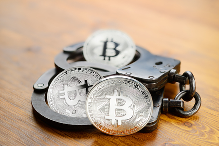 Silver Bitcoin coins and handcuffs on wooden table. Law problems or arrest concept Stock Photo