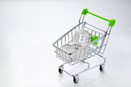 Silver Bitcoin coin in the shopping cart. Trading or buying concept  Stock Photo