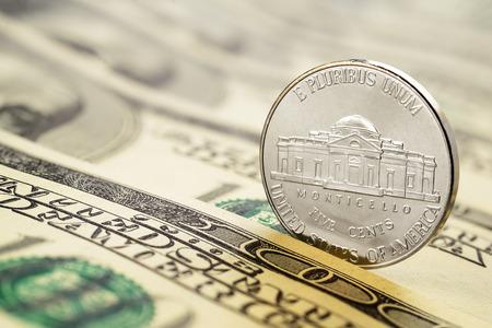 us coin: Five cents nickel US coin on hundred dollar bills. Macro shot