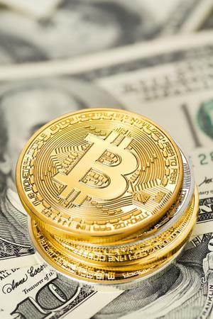 Golden Bitcoin stack on US dollar bills. Electronic money exchange concept