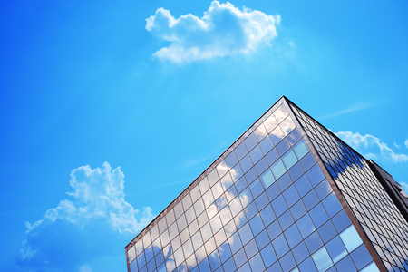 Glass blue windows office building with sky and clouds mirroring