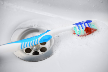 Gum disease concept. Blue toothbrush with toothpaste and blood near washbasin sink Stock Photo
