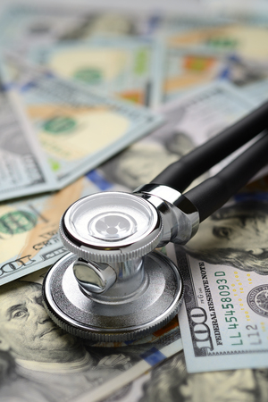 Medical stethoscope on heap of dollar bills. Health care or insurance costs concept. Finance banking audit analytics. Stock Photo