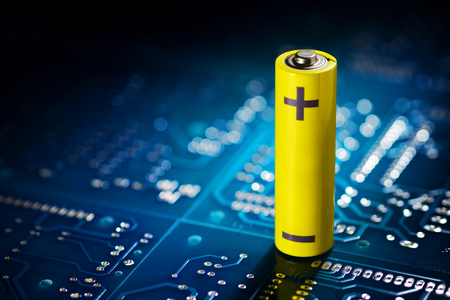 Yellow mignon AA battery on the blue printed circuit board. Macro shot