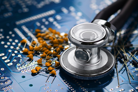 Medical stethoscope and electronic components on the blue printed circuit board Stock Photo