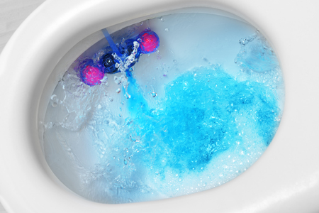 Toilet bowl with cleaner and freshener block, flushing blue water