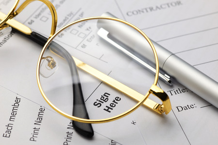 Sign here word on business documents with eyeglasses and ballpoint pen. Signature or agreement concept