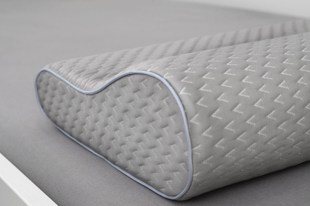 Gray orthopedic pillow made of memory foam on the bed. Slose-up shot