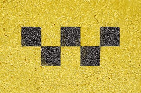 Black taxi checks symbol on the yellow asphalt road surface Stock Photo