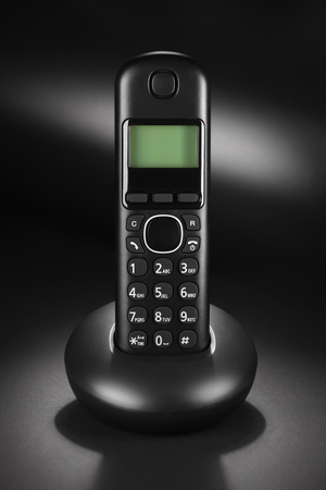 Cordless phone on black background with empty space for your text