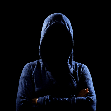 Silhouette of unrecognizable woman in hoodie on black. anonymous or criminal concept