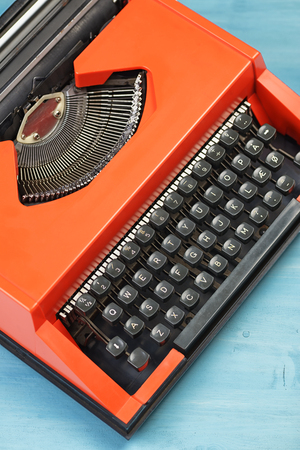 Red typewriter on the blue desk or table. Top view