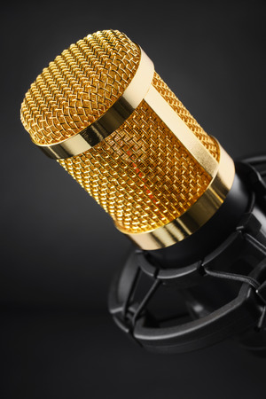 Gold colored condenser microphone other black background. Sound recording equipment. Imagens