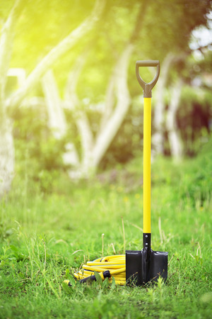 Yellow shovel and hose pipe in the garden with green grass and trees