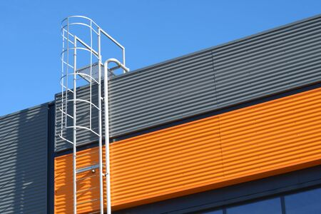 Metal fire escape stairs or ladder to roof on a wall of building Imagens