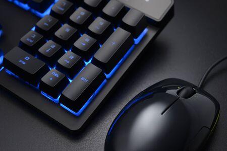 Touches numériques du clavier noir et souris filaire sur le bureau sombre