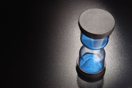 Hourglasses with blue sand measuring passage of time on black background Stock Photo