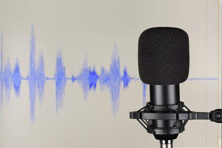 Black studio condenser microphone over computer monitor background with waveform. Sound recording concept
