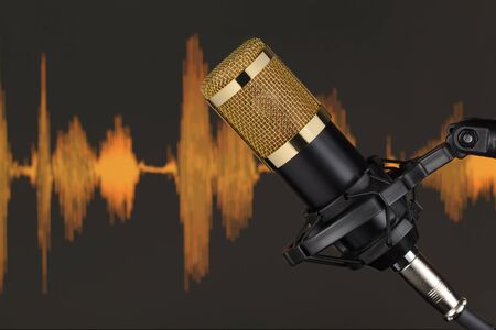Gold colored condenser microphone over computer monitor background with waveform. Sound recording concept